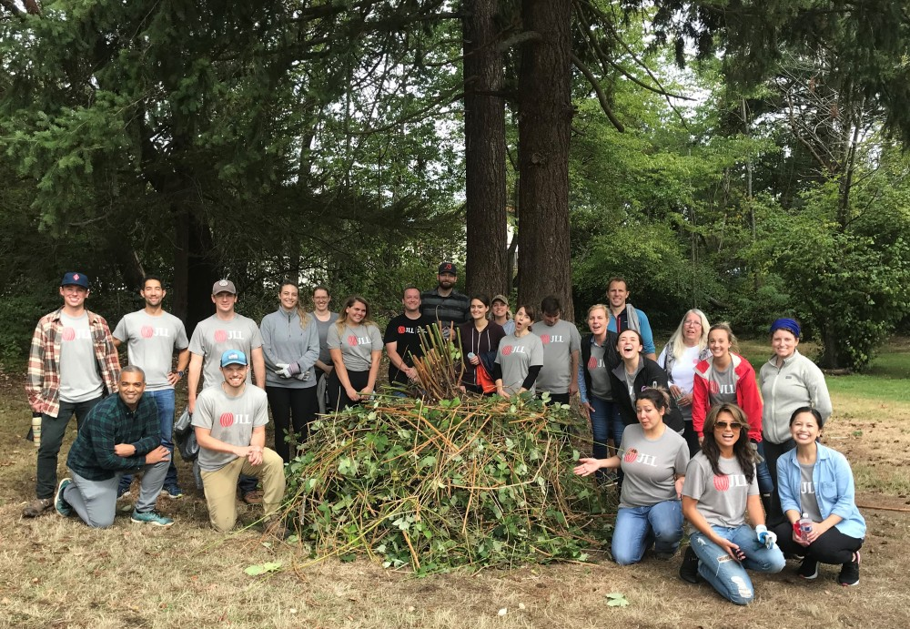 Group of 23 adult volunteers with pile of invasive blackberry weeds at Dick Thurnau Memorial Park.