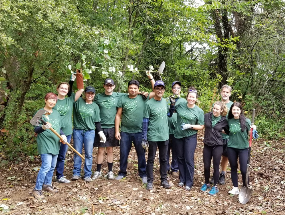 Group of 11 adult volunteers with pile of invasive blackberry weeds at Dick Thurnau Memorial Park.